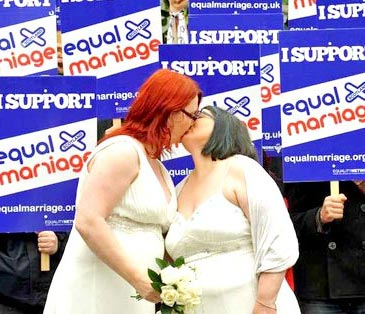 A lesbian couple kiss at a marriage equality rally outside the Scottish Parliament