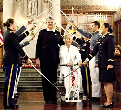 Brenda Sue Fulton, center left, and Penelope Gnesin, proceed through an honour guard forming an arch of raised swords after exchanging wedding vows at West Point. (AP Photo/Outserve-SLDN, Jeff Sheng)